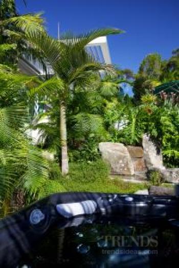Tropical garden with pools, waterfalls, bridge, bush paths, spa pool