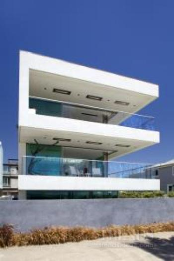Modern beachfront house with pivot walls, light-filled atrium, large terraces