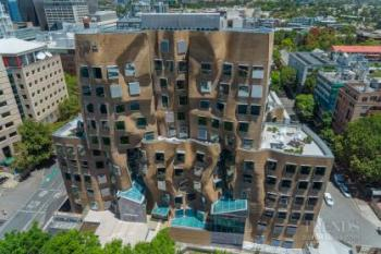 Building by architect Frank Gehry with undulating brick facade, angular glass shards