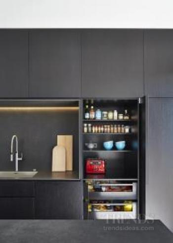 Sleek black kitchen by owner-architect with black porcelain slab benchtops, dark veneer cabinets