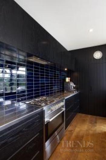 Black kitchen in black house designed by owner-designer David Ponting references the '50s