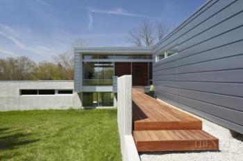 Contemporary, transparent house with aluminium and concrete sidings, connected garage and river views