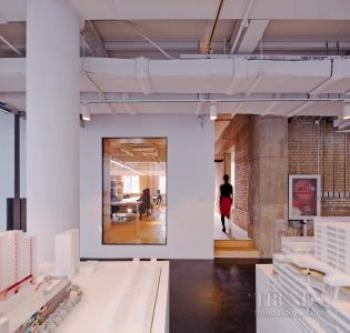Architectural office in older building, exposed brickwork and services, glass box annex