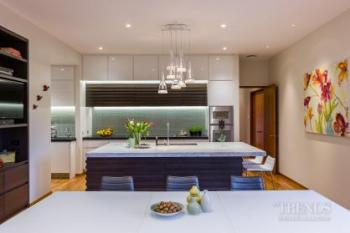 Contemporary, open-plan kitchen with battens on island and variety of benchtops