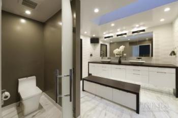 Modern white bathroom with textured tiles, shower zone and central bench with storage