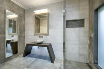 Modern bathroom with switch glass, minimalist vanity, and large tiles