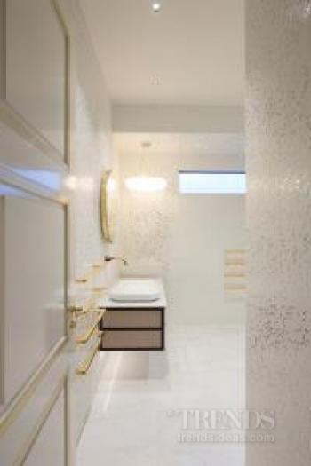 Gold accents, mirror-front drawers, and stone floors contribute to a high-end ambience in this ensuite