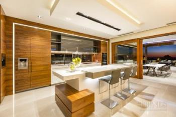 Modern kitchen with rich custom cabinetry and seamless link to outdoor area. Image: 3
