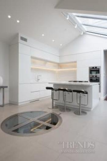 Light, white kitchen has adjacent underground wine cellar
