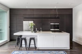 Kitchen renovation combines understated white island with dark wood cabinetry kitchen. Image: 1