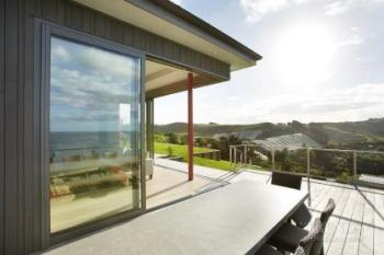 Wall-size corner sliding glass panels merge indoors with outdoors
