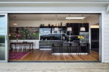Clean-lined black kitchen designed to complement the owners' artworks