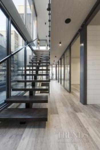 New glass walled apartment rises from steel structure of warehouse conversion below