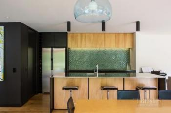 Green tile splashback creates a natural feel in this affordable kitchen