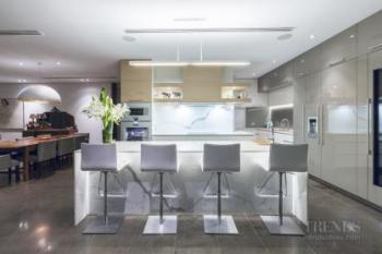 Clean lined modern kitchen is served by a large scullery behind