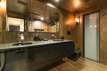 Dramatic bathroom with rust look tiles and black accents