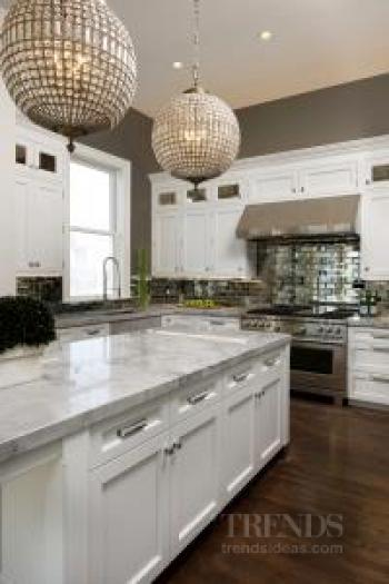 Antique mirror tiles and traditionally built cabinetry are features of this kitchen