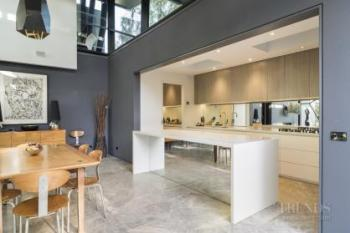 White and wood kitchen features skylights and mirror on splashback and island front