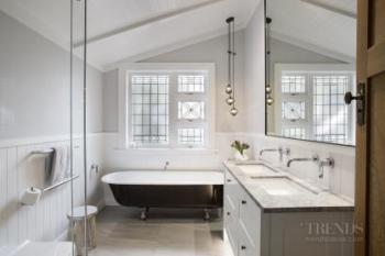 White bathroom with lead light window and undermount basins balances modern with traditional