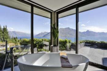 Large window walls in master ensuite make the most of mountain and lake views