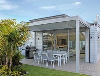 A louvre roof with drop-down screen gives this home a year-round outdoor dining space