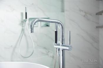 Pared back design with marble-look tiles creates luxury aesthetic for renovated villa bathroom