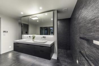Dramatic interplay of texture and tone play a leading role in this pared-back master bathroom