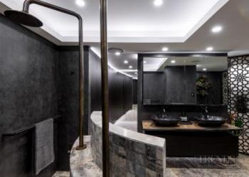 Stone, bronze, wood and metallic-hued tiles combine to exotic effect in this luxury ensuite