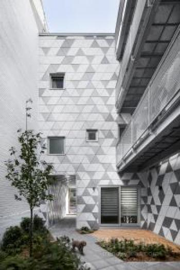 Rough brick facade fronts an innovative apartment building with a communal courtyard at its heart
