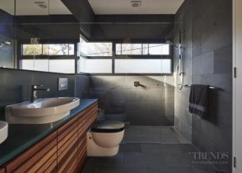 Townhouse bathroom includes concealed laundry entered via a hidden door