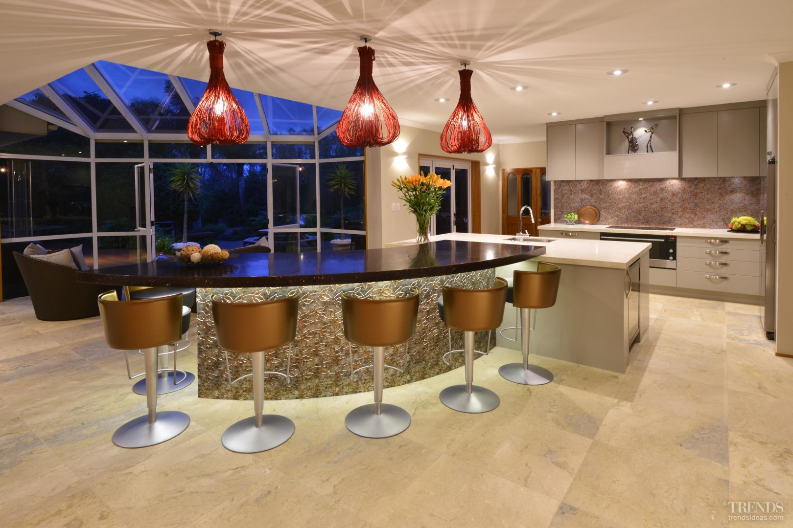 renovated kitchen with metallic curved island front and patterned renovated kitchen with metallic curved island front and patterned glass splashback