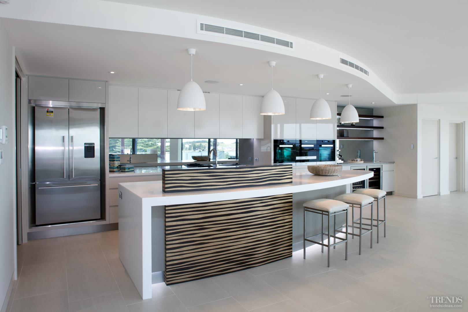 New penthouse kitchen with curved island and wood veneer upstand with metallic finish