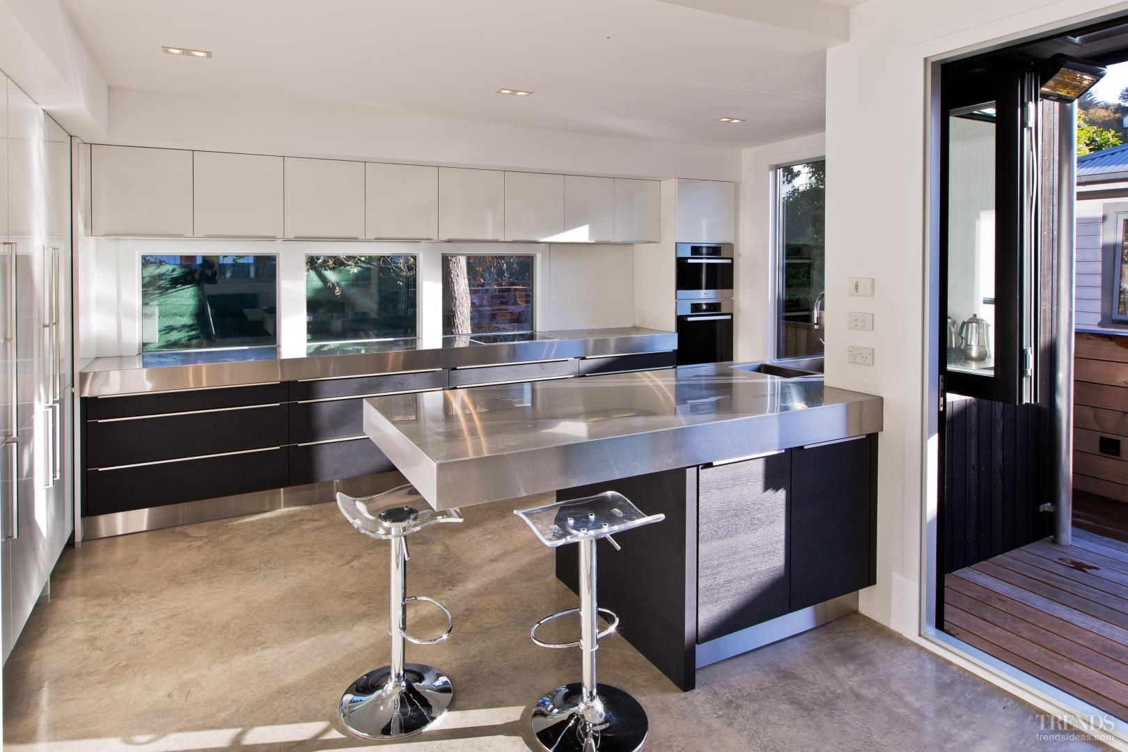 Open contemporary kitchen with stainless steel benchtops and