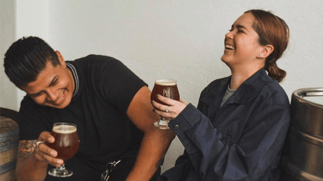 couple laughing while drink a beer