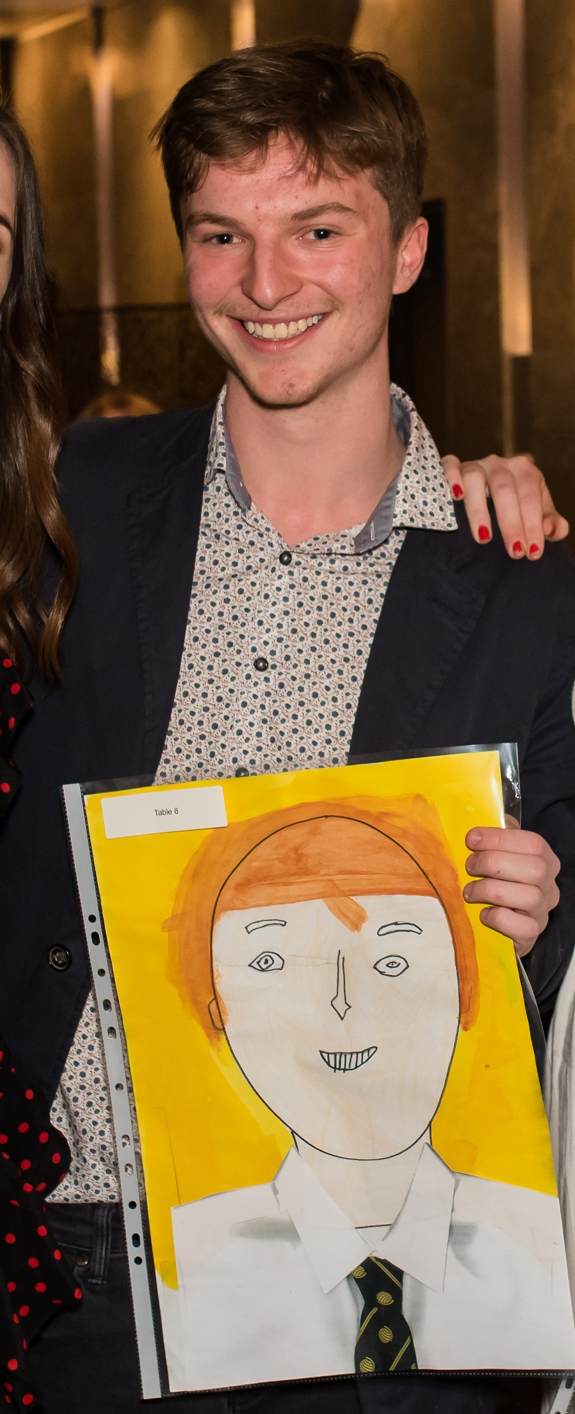 Davis Evans at the IGS graduation dinner with a portrait of him painted by a Year 1 student