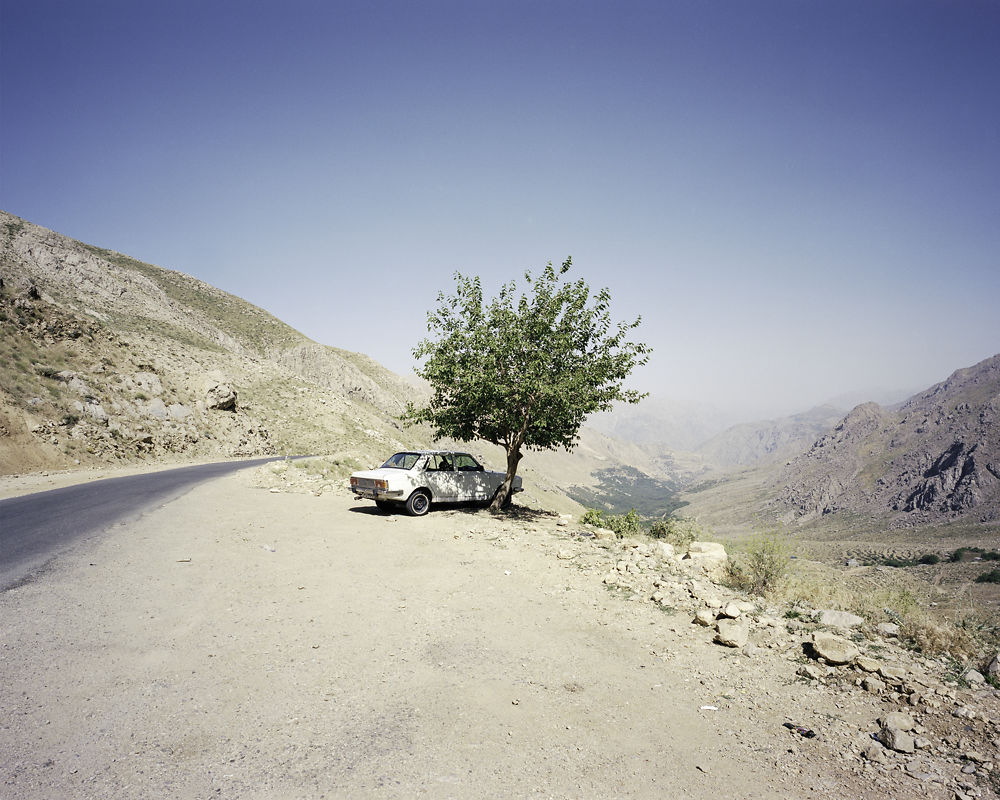 A family's Paykan (translated from Farsi as 'Arrow') sits beneath a tree overlooking the Hawraman Valley, Kurdistan.