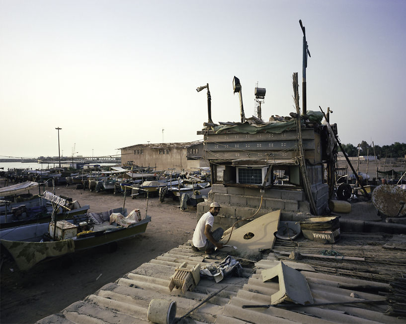 The boat yard manager toying with his aircon unit to his apartment, Hormuz.
