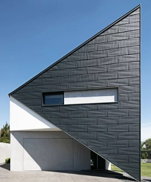 reform architekt's triangular house in poland perfectly fits surrounding environment