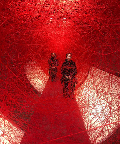 chiharu shiota weaves webs around two seated performers, 100 years after WWI