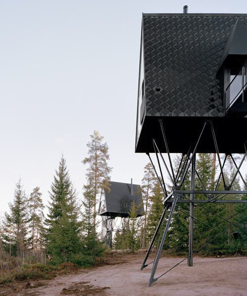 all-black stilted cabins by espen surnevik are elevated among the trees
