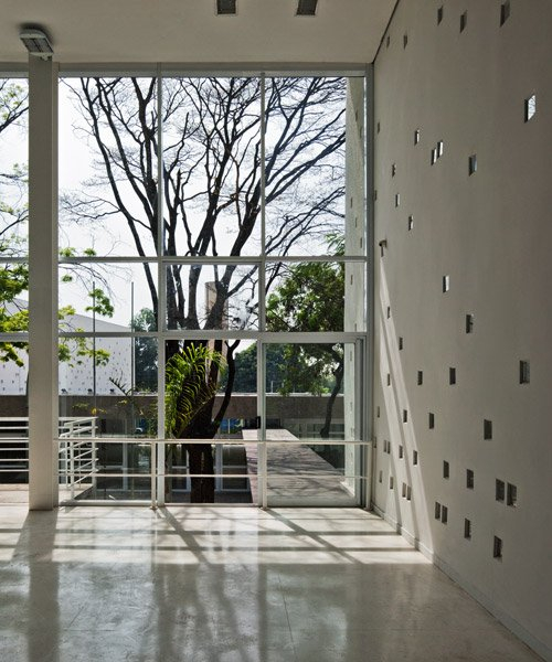 carolina penna architects designs a training center around existing trees in brazil