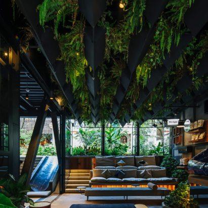 Plants cover grey steel of Hotel Click Clack Medellín by Plan:b Arquitectos