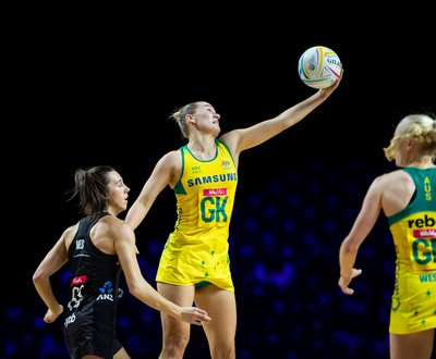 Bryce Courtney, goal keeper, holds ball while two netballers watch image
