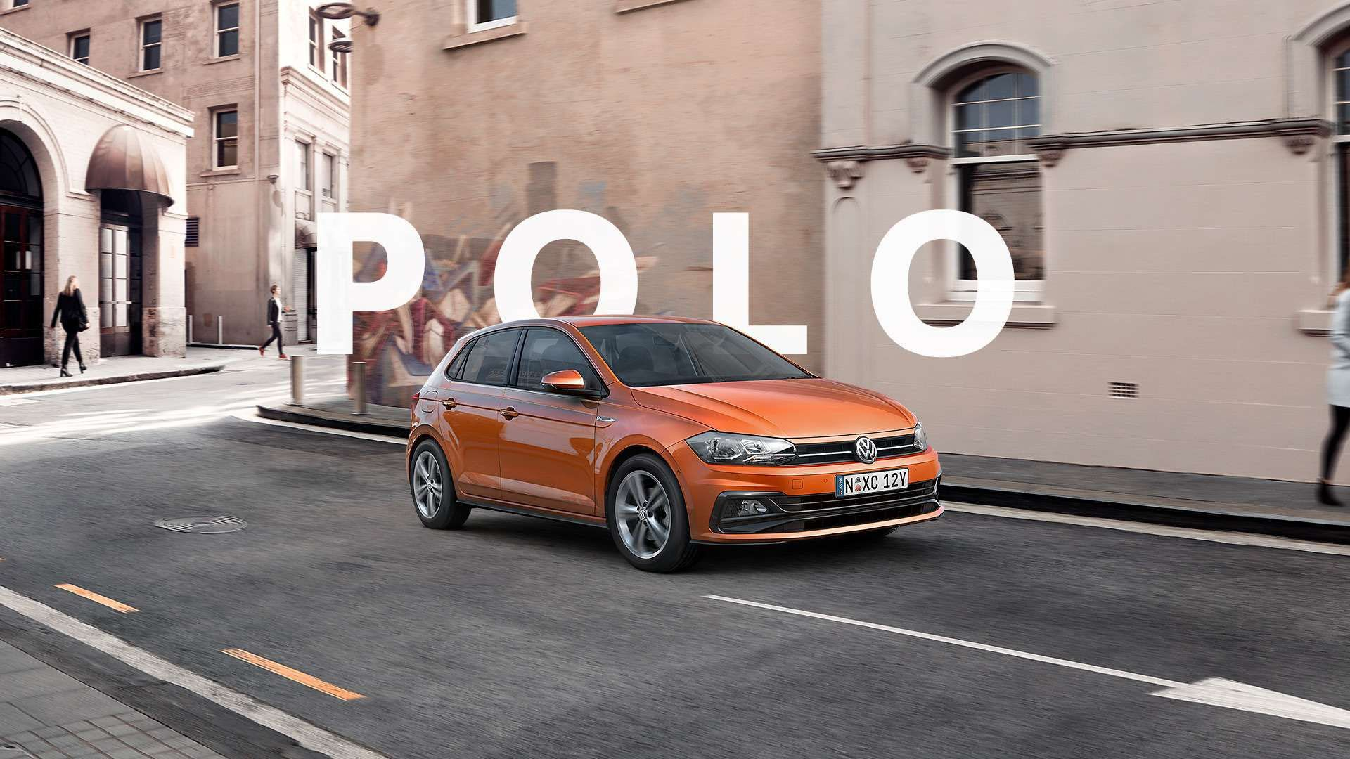 Energetic orange metallic Polo driving through street.