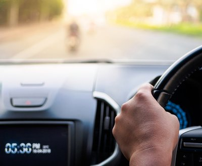 POV shot of hand on steering wheel image