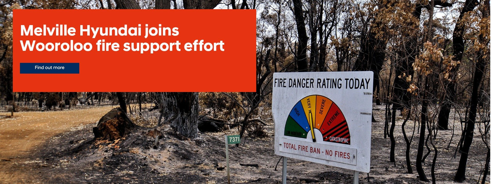 Patch of burnt bushland with fire danger sign standing off to one side