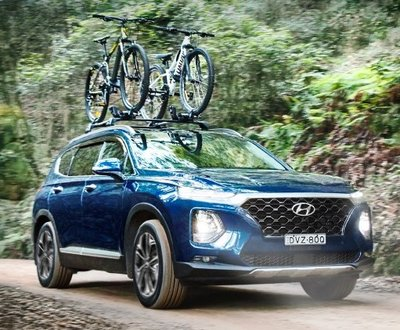 Santa Fe with bicycles trapped to its roof racks driving through the forest image