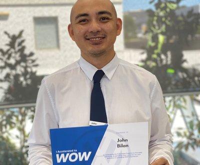 John Bilan holding his wow certificate for providing premium customer service image