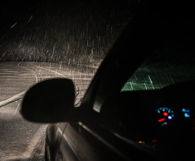 Perspective shot of car driving through snow at night with low visibility  image