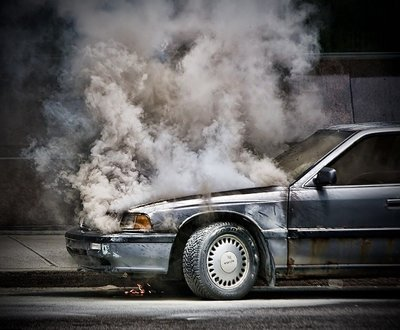 Silver car broken down on roadside smoking from under hood image